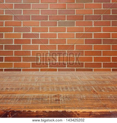 Empty wooden table over red brick wall