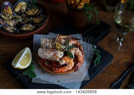 Tapas with shrimp and squid on wooden board, from top.