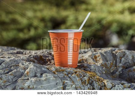 Brown Plastic Coffee Cup With A Spoon On A Rock On A Background