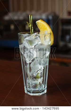 Highball Glass With Ice And A Yellow Tube On The Wooden Bar