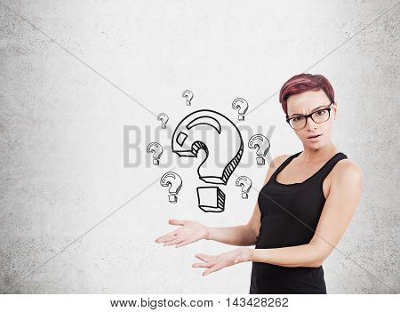 Woman standing near concrete wall with question marks sketches on it showing them to viewer. Concept of decision making. Mock up