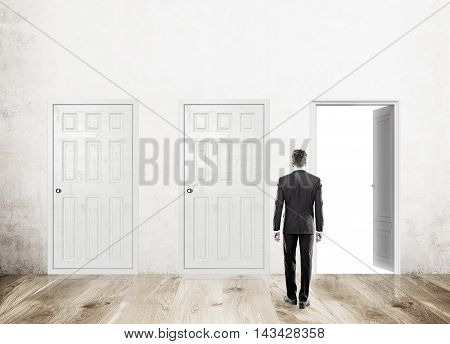 Man standing with back to camera in corridor with three doors one open. Wood floor. Concept of decision made. Mock up