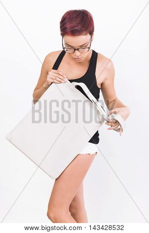 Girl with short red hair holding cotton textile bag. She is wearing black tank top and tiny white shorts. Concept of insert your product image here. Mock up. White background.
