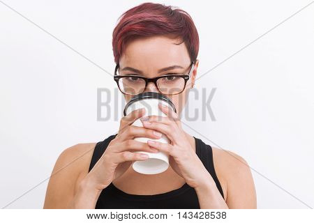 Woman in nerd glasses with short red hair is holding large paper cup of coffee and drinking from it. Concept of energetic drink. Mock up. White background.