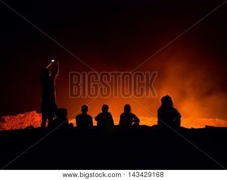 ERTA ALE ETHIOPIA - JUNE 28 2016: Tourists sitting at the edge of Erta Ale active volcano in Afar Region in Ethiopia Africa at night.