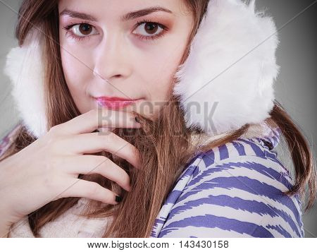Teenage girl wearing fluffy white earmuff in winter fashion freezing cold time.