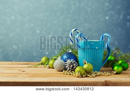 Christmas decorations with blue cup on wooden table over bokeh background