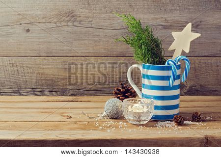 Christmas decorations with tee cup over wooden background