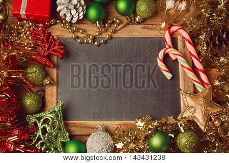 Christmas holiday background with blank chalkboard and Christmas decorations. Border design with copy space in the middle.