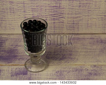 Black Currant On A Wooden Background.