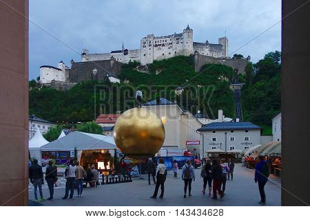 Salzburg, Austria, August 6, 2016: The Chapter Square with the artwork «Sphaera» and the castle on the hill in Salzburg, Austria.