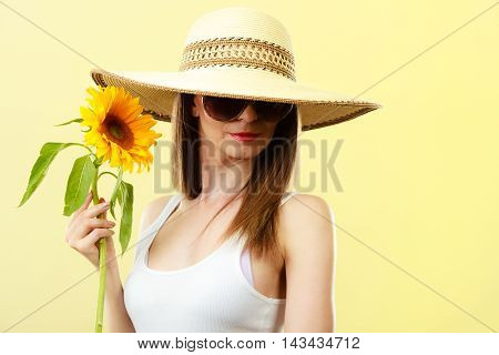 Closeup of attractive summer woman in sunglasses straw hat with sunflower in her hand on yellow background