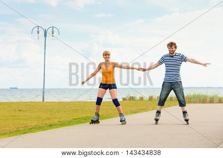 Active lifestyle people and freedom concept. Young fit couple on roller skates riding outdoors on sea coast woman and man rollerblading enjoying time together