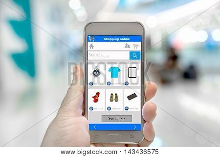 Smart phone online shopping in man hand. Shopping center in background. Buy clothes shoes accessories with e commerce online shopping website