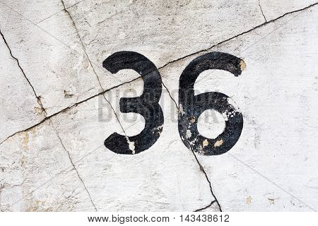 number 36 painted on a cracked house wall