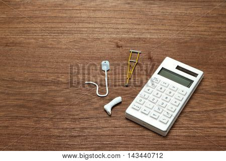 Miniature items of illness or injury beside calculator. Injury, illness, medical, insurance concept.