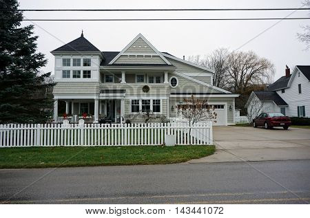 WEQUETONSING, MICHIGAN / UNITED STATES - DECEMBER 22, 2015: A large home with a white picket fence and an attached garage on Pennsylvania Avenue in Wequetonsing.