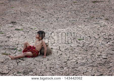 Children sit down in the dried soil in arid season.
