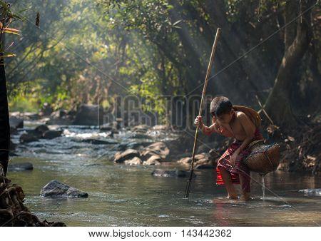 Fisher boy hunter fishing gaff in the waterfall.
