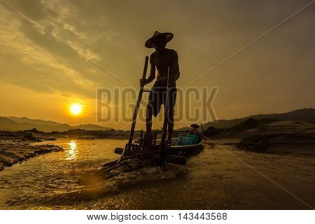 Fishermen throwing fishing net during sunrise, Thailand
