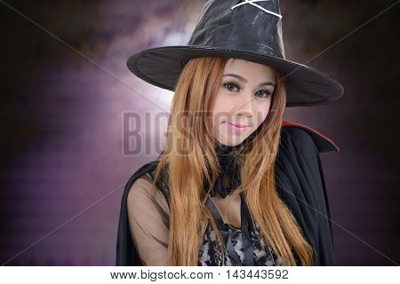 Pretty girl in witch costume for halloween night in dark background.