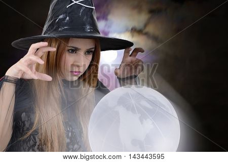 Witch casts a spell to the earth in dark background.