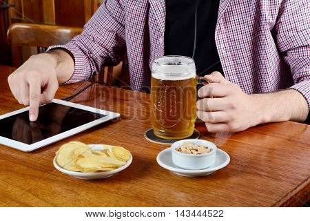 Portrait of young latin man drinking beer with digital tablet and snacks. Indoors.