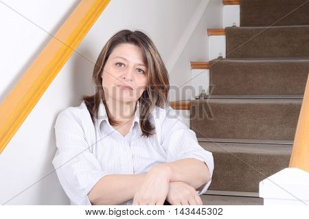 Portrait of beautiful businesswoman relaxed sitting on stairs at home. Indoors.