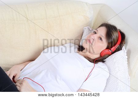 Portrait of a beautiful woman listening to music and relaxing on the sofa. Indoor.
