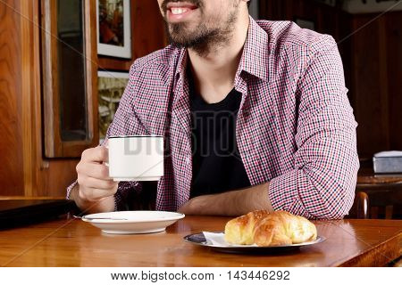 Portrait of young latin man drinking coffee at a cafe. Indoors.