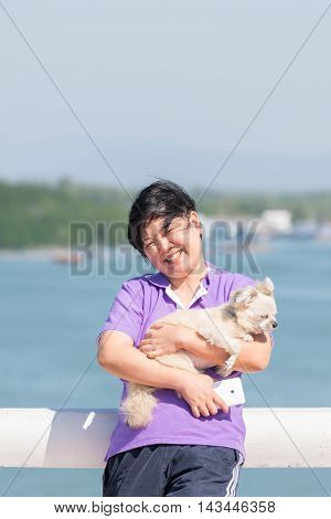 Asia Woman And Her Dog Standing At Estuary (river Side And Sea)