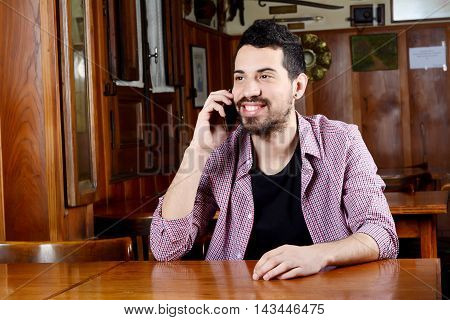 Portrait of young latin man talking on the phone in a cafe. Indoors.