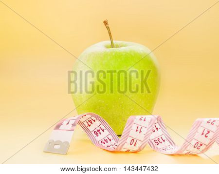 Measuring tape and delicious green apple on bright yellow background. Diet or healthy eating concept.