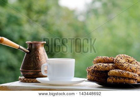 White mug with coffee Cezve and a plate of cookies on the table