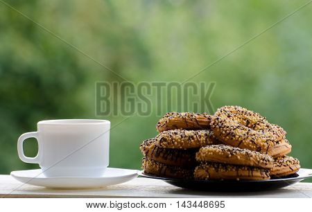 A mug of coffee and a plate of delicious cookies on the table green background