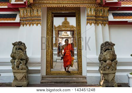 Bangkok Thailand - Dec 24 2015: Buddhist monk in orange robe go through doorway in Wat Pho temple inner yard