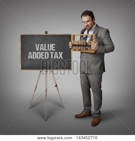 Value added tax text on blackboard with businessman and abacus