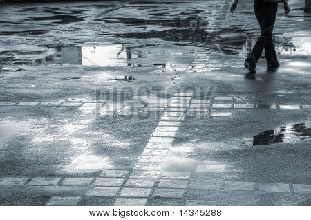 Person walking through puddles on a wet sidewalk