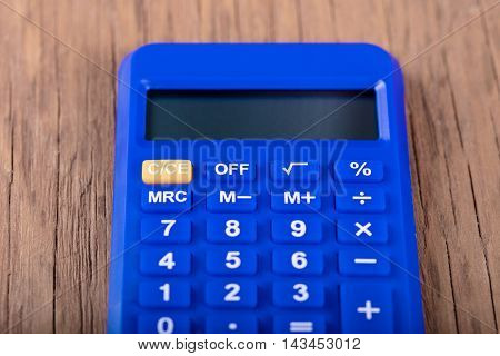 blue calculator closeup on the wooden background