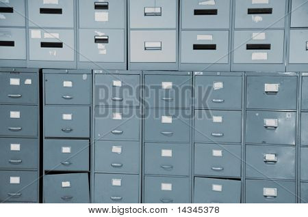 Wall of old gray metal filing cabinets drawers