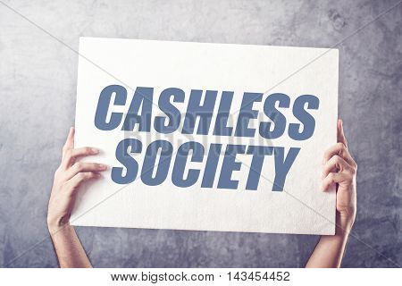 Hands holding banner with Cashless society title concept of promoting mobile and electronic payments without cash money banknotes