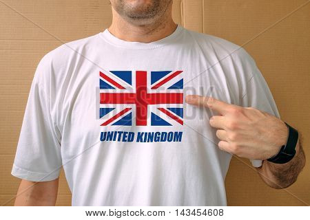 Handsome man proudly wearing white t-shirt with United Kingdom flag printed on chest concept of patriotism national pride and love for Great Britain