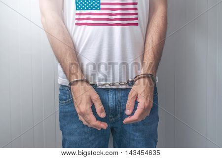 Arrested man with cuffed hands wearing shirt with USA flag. Unrecognizable male person in jeans with handcuffs held in police station for being suspected of a crime.