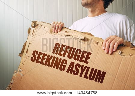 Refugee seeking asylum in foreign country male immigrant with cardboard banner