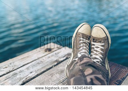 Man with crossed legs relaxing on riverbank pier casual young guy wearing sneakers sitting by the river in summer afternoon selective focus