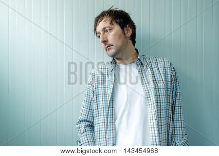 Sad and blue man male person with unhappy gloomy facial expression leaning on to wall and looking to a side.
