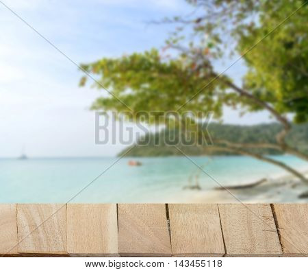 wood table top on blur background of seascape for feel good to relax on morning clear blue sky and sea - can use to display or montage on product