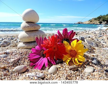 Stone stack or stack rock of pebbles at the beach with colorful flowers. Balanced stones.