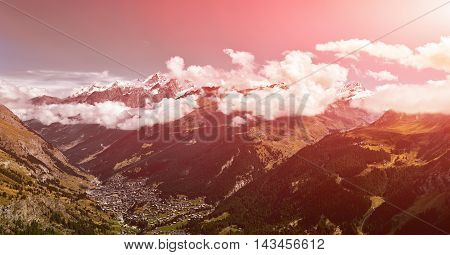 Snow capped alpine mountains and valley with Zermatt town. Trek near Matterhorn mount.