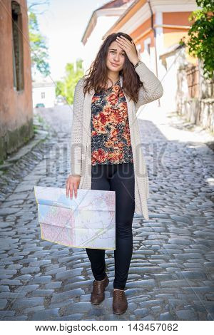 young desperate girl tourist with a map